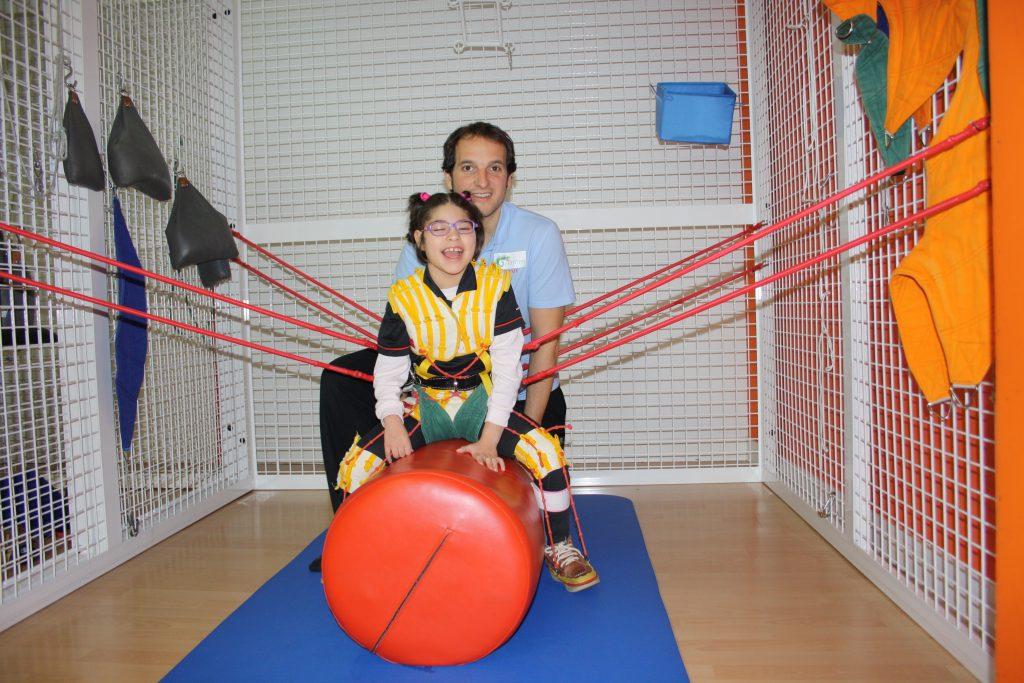 Fisioterapeuta empleando el método Therasuit con una niña