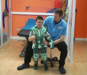Terapeuta posando con un niño que viste el traje Therasuit